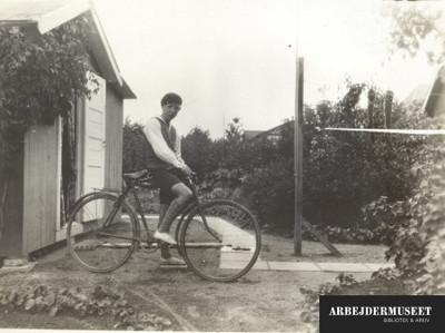 Dreng med sin cykel foran kolonihavehus, han er iført korte bukser lange strømper og alpehue
