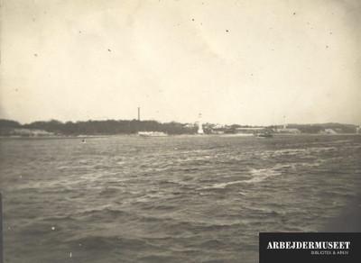 Kystnært eller bred flod, i baggrunden noget der ligner fyrtårn og på vandet ligner det en bugserbåd