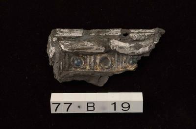Onvolledig sierbeslag in verzilverd en verguld brons met inlegwerk in glas
