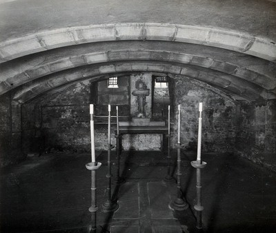 The church of St. Bartholomew the Great; interior of the crypt with two lines of long candlesticks in their holders. Photograph by W.F. Taylor.