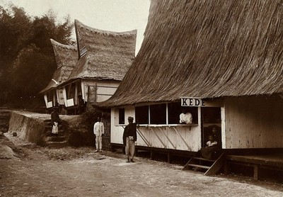 Boarding houses for visitors to the local leper asylum, next to the village shop; the buildings have tall, pointed thatched rooves. Photograph, 1890/1910.