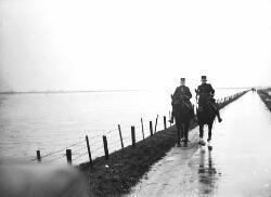 Hoogwaterperiode 1930, politie surveilleert op de dijken.