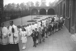 Eerste Heilige Communie, kinderen netjes in een rij met nieuwe kleren, o.a. Antoon Spierings. Rechts staat de kleuterschool naast Huize Mariënhof.