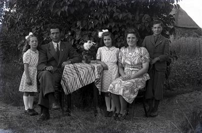 Een groepsfoto rond een tafel in de tuin; de meisjes dragen strikken in het haar. Weet iemand wie dit zijn en ter gelegenheid waarvan deze foto is gemaakt?