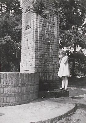 Dochter Annie v.d. Heuvel Tini drinkt water uit de kraan van het Kolonel Thomsonmonument.