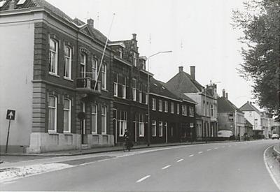 Straatbeeld met panden langs de Taalstraat ter hoogte van de kruising met de Zeeldraaierstraat; het pand links heeft een balkon en een vlaggenstok.