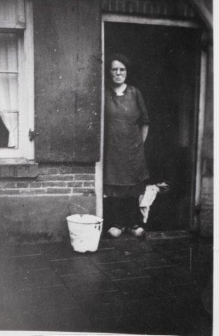 Vrouw met wasmand in een deuropening