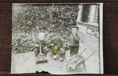 Drie kleuters bij een woonhuis