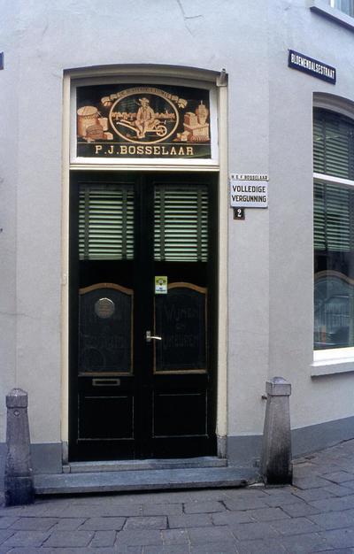 Voordeurpartij van Bloemendalsestraat 2, café P. J. Bosselaar, op de hoek van 't Zand, met versierd bovenlicht.