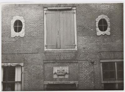 Deel voorgevel van Krommestraat 36: brouwerij De Kroon uit 1663. Ovale ramen met cartoudches, gebeeldhouwde gevelsteen, laad- en losraam met luiken.           Rijksmonument.