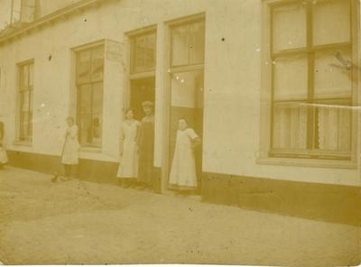 Schoenmaker Van de Veer voor zijn werkplaats aan de Muurhuizen 113. Wie de vrouwen zijn is onbekend (hij was ongehuwd).