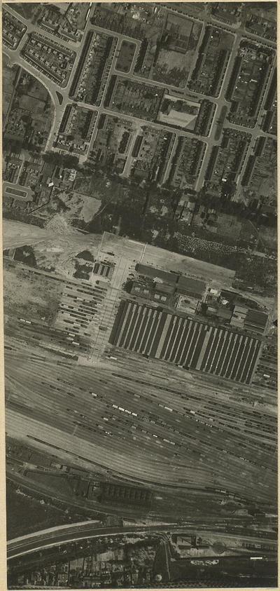 Luchtfoto van het spoorwegemplacement met de kruising van de spoorlijnen naar Utrecht en Amsterdam. Daarboven gebouwen van de Wagenwerkplaats en het Soesterkwartier met de           Palmstraat (links), de Soesterweg en een deel van de Bloemenbuurt. Helemaal onder woningen aan de Barchman-Wuytierslaan. Deze foto is het linker exemplaar van een stereoscopisch paar,           namelijk Vluchtbaan 4, nummer 69.