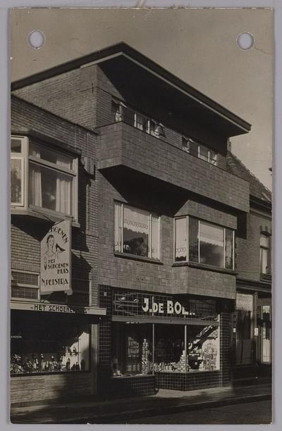 Onbekende locatie. Links Het Schoenenhuis van N. Petstra, rechts een comestibleszaak van J. de Boer.