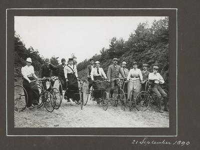 De Baarnsche Vélocipede-Club met haar fietsen op een weg door bos en hei. Vijfde van rechts, in geruit kostuum: Gerard Adriaan Pos, één van de oprichters van de           ANWB.