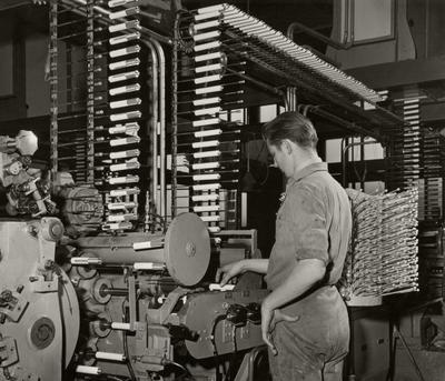 Onderdeel van een installatie voor de vervaardiging van lege tubes. Met een minimum aan handwerk wordt een capaciteit van dertig millioen tubes per jaar           bereikt.