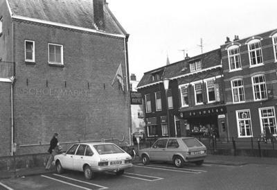 Parkeerterrein aan de Mooierstraat, Amersfoort. Gezien in de richting van de Kortegracht. Links Schoenmarkt De Kortegracht (nr. 3). Op deze plek stond tot begin jaren '60           het postkantoor, daarna Reproka. Rechts op de achtergrond het zwart geschilderde pand waar destijds fotograaf Paul de Smalen zat (nr. 6). Op de plaats van de foto is later het winkelcentrum           Drakennest gebouwd.