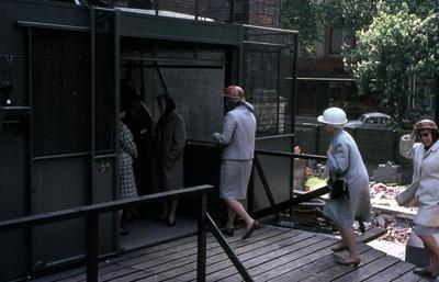 Een gezelschap betreedt een liftkooi tijdens restauratiewerkzaamheden aan de Onze-Lieve-Vrouwetoren. Het merendeel van de mensen heeft een helm op. Geheel rechts: Rie van           Hoogevest- Bruijn. Voor haar, met witte hoed: Geer Mooijen- van Hoogevest (zuster van Gijs van Hoogevest). Daarvoor Riet Ruitenberg- van Hoogevest (echtenote van de           fotograaf).