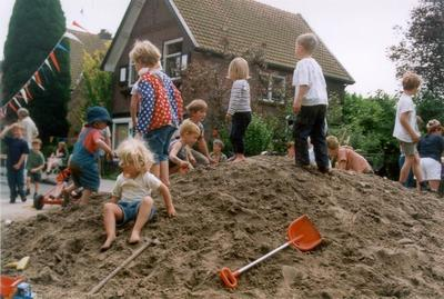 Kinderen spelen op een zandberg in de Bernulfusstraat. Het zand is daar gestort vanwege een buurtfeest.