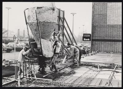 Bouwvakkers aan het werk bij de nieuwbouw van het Stadskantoor aan de Stadsbrink. Opnamerichting in zuid-westelijke richting