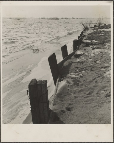 De Rijn met oeverbeschoeiing. De rivier is dichtgevroren.