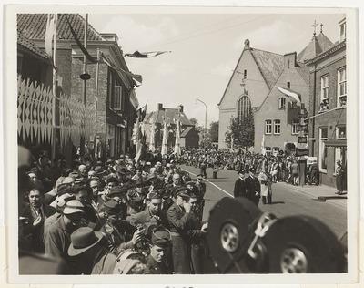 Defilé tijdens de viering van 10 jaar bevrijding tegenover Hotel de Wereld. Op de achtergrond is de Rooms Katholieke Kerk aan de Bergstraat zichtbaar.