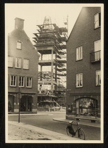 Blik op de herbouw van toren bij de Nederlands Hervormde Kerk aan de Markt. Foto genomen uit de Rouwenhofstraat, richting zuid-oosten. In het pand rechts is een banketbakkerij           gevestigd.