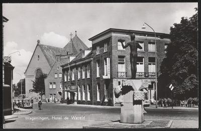 Oostgevel en voorgevel van Hotel de Wereld aan de Generaal Foulkesweg (voorheen Rijksstraatweg) gezien richting het noord-westen. Op de voorgrond staat 'Blote Jan',           herdenkingsmonument van de Tweede Wereldoorlog door Han Richters.