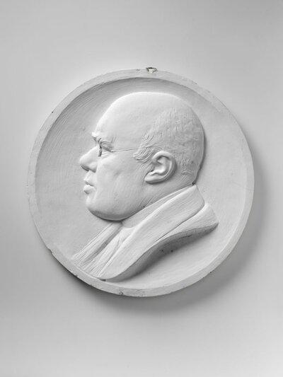 Naar links gericht profiel van dr. H.J.A.M. Schaepman (Tubbergen, 2 maart 1844 – Rome, 21 januari 1903). Herman Schaepman was een Nederlands dichter, rooms-katholiek           priester, theoloog en politicus. Hij speelde een doorslaggevende rol in de katholieke emancipatie als eerste priester die lid van de Tweede Kamer werd.