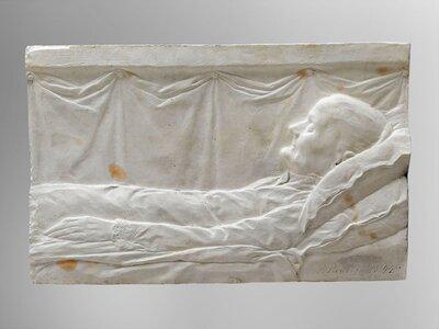 Op een bed gelegen oude vrouw met gesloten ogen.
