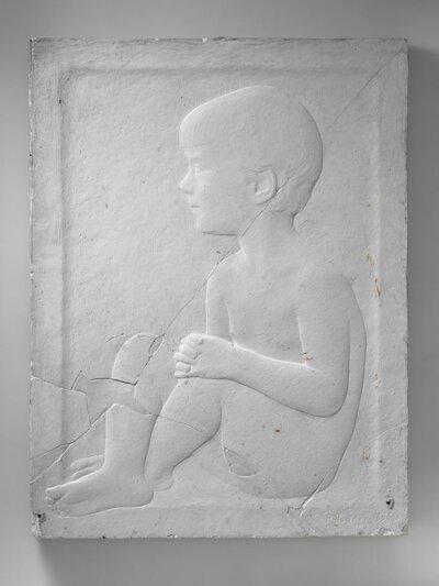 Portret van een zittende jongen voluit. Naar links gericht en profile.