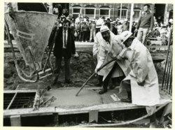 Wethouder G.H.C. Halleen stort het eerste beton voor een nieuwe gymzaal, waarboven acht woningen, tussen de Terwestenschool en de Honthorststraat