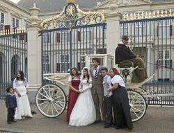 Een bruidspaar laat zich met familieleden fotograferen tegen de achtergrond van paleis Noordeinde