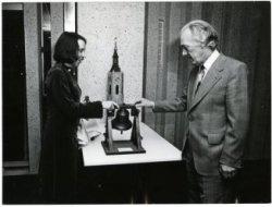 De beiaardier Henk Herzog neemt afscheid als beiaardier van de Grote Kerk en bekijkt met zijn opvolgster, Heleen van der Weel, een miniatuur klokkenstoel, één van de           geschenken tijdens zijn afscheidsreceptie in het stadhuis aan de Groenmarkt
