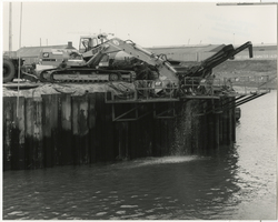 Verankeren van de damwand in de doorgang van zwaaikom naar Eerste Vissershaven. Foto uit de reportage Verbetering havenmond en Eerste Vissershaven van Scheveningen. Omdat           steeds grotere trawlers en kustvaarders de haven van Scheveningen aandoen, werd in augustus 1988 een begin gemaakt met de werkzaamheden ter verbetering van de toegang en ter voorbereiding           van het uitdiepen van de Eerste haven van 6 tot 8 meter. De werkzaamheden werden eind mei 1989 beëindigd