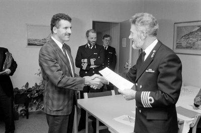 Blijk van waardering voor eervolle en langdurige dienst (bij officieren van de Nederlandse krijgsmacht het officierskruis of ook wel 'het jeneverkruis' genoemd) van de           commandant van het Commandement Maritieme Middelen Den Helder (CMMHELDR) kapitein-ter-zee M.C. Bakker (1939, rechts) in december 1989. Derde van rechts kapitein-luitenant-ter-zee E.H.G.           Michelhoff (1940).