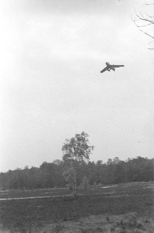 Een Republic F-84 jacht-bommenwerper (Thunderstreak) van de Kon. Luchtmacht vliegt laag over tijdens een oefening met militairen van de Kader School           Infanterie.