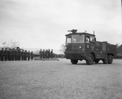 Commandant CLO bëedigt 26 officieren. Plechtigheden op 8 november 1957 op de vliegbasis Deelen. Commodore-waarnemer (C-CLO) W. den Toom neemt de eed af van 26 nieuw benoemde           officieren.De troepen staan in carré waar tevens twee Harvard lesvliegtuigen staan opgesteld.Hier het defile met een brandweerwagen.