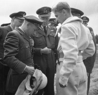 Z.K.H. Prins Bernhard brengt in zijn hoedanigheid van Inspecteur-Generaal van de Koninklijke Luchtmacht een werkbezoek aan de vliegbasis Leeuwarden. Hier krijgt de prins           uitleg over de kledij van een brandweerman.