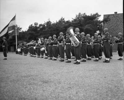 Commandant CLO bëedigt 26 officieren. Plechtigheden op 8 november 1957 op de vliegbasis Deelen. Commodore-waarnemer (C-CLO) W. den Toom neemt de eed af van 26 nieuw benoemde           officieren.De troepen staan in carré waar tevens twee Harvard lesvliegtuigen staan opgesteld.Hier de muzikalen omlijsting.