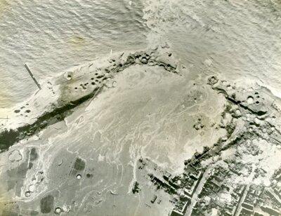 Fotoafdruk zwart-wit betreffende bombardementen van de Royal Air Force, Walcheren.Zeewater stroomt Walcheren binnen door het gat in de dijk bij           Westkapelle.