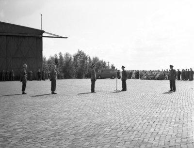 Opname van de plechtigheden op de vliegbasis Woensdrecht waar op 26 augustus 1958 het commando over de vliegbasis zal worden overgedragen door commodore-waarnemer W. de Toom           (rechts) aan kolonel-vlieger W. Bakker (links). Tevens zal op deze dag de beëdiging plaatsvinden van 17 officieren.