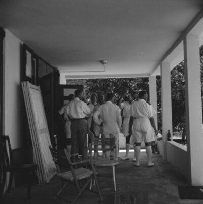 De commandant van kruiser Hr.Ms. De Ruyter (C 801) kapitein-ter-zee A.H.J. van der Schatte Olivier (1908-1967, vierde van rechts) en de eerste officier           kapitein-luitenant-ter-zee J.W. Caspers (1909-1990, rechts) op de veranda van een guesthouse op St. Maarten, oktober 1955.