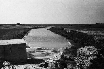 De tankgracht in de vallei van de Molenbeek, ten zuiden van Bergen op Zoom, gezien vabaf de weg Bergen op Zoom-Hoogerheide in de richting van de Schelde. Achter het huisje           links op de achtergrond loopt de spoorlijn naar Zeeland.<br>