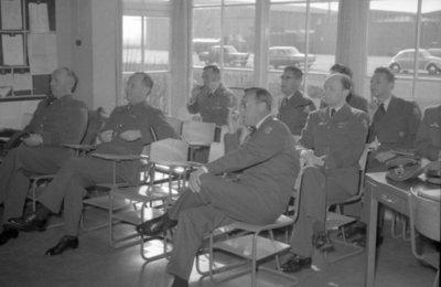 Z.K.H. Prins Bernhard, Inspecteur-Generaal van de Koninklijke Luchtmacht bracht op 10 maart 1959 een bezoek aan de vliegbasis Eindhoven waar hij in een door hem zelf           gevlogen T-33 arriveerde. De prins bezocht diverse onderdelen en diensten van de basis. Bezocht werden 314 en 315 squadron en na aldaar een demonstratie van ATO-starts en een scramble van           tweemaal 6 F-84F's te hebben bijgewoond, vervolgens de verschillende andere afdelingen. Op de foto: de prins luistert met zijn gevolg naar de briefing van de basiscommandant kolonel           Kramer.