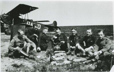 Zeven vliegers/anderen poseren tijdens een oefening voor de Fokker C.I met opschrift/registratie Radio. Op de foto zijn de volgende namen geschreven: K. van Vliet, A. Copes           van Hasselt, Van Weeren, S. Schimmelpenninck en Peters. Groepsfoto.