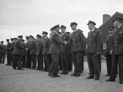 Commandant CLO bëedigt 26 officieren. Plechtigheden op 8 november 1957 op de vliegbasis Deelen. Commodore-waarnemer (C-CLO) W. den Toom neemt de eed af van 26 nieuw benoemde           officieren.Felicitaties aan de pas benoemde officieren.