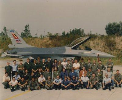 Een General Dynamics F-16A Fighting Falcon in MLU Çheck Six' outfit. Het gaat hier om het update programma van de diverse luchtmachten (MLU) Mid Life Update voor onder           andere de Verenigde Staten, België, Denemarken, Nederland en Noorwegen, later sloot Portugal zich hierbij aan. Op de voorgrond poseert het personeel van de diverse luchtmachten die           deelnemen aan het programma.<br>