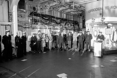 De bemanning van het S-fregat Hr.Ms. Kortenaer (1978-1997) ontvangt ter gelegenheid van de Kerstviering 1989 gasten, die door de commandant van de Kortenaer           kapitein-luitenant-ter-zee F.O. Laks (1945, achter katheder) in de scheepshangar worden toegesproken.