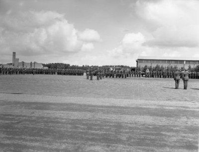 Opname van de plechtigheden op de vliegbasis Woensdrecht waar op 26 augustus 1958 het commando over de vliegbasis zal worden overgedragen door commodore-waarnemer W. de Toom           aan kolonel-vlieger W. Bakker. Tevens zal op deze dag de beëdiging plaatsvinden van 17 officieren.Op de achtergrond Gloster Meteor straaljagers.