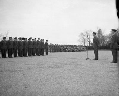 Commandant CLO bëedigt 26 officieren. Plechtigheden op 8 november 1957 op de vliegbasis Deelen. Commodore-waarnemer (C-CLO) W. den Toom neemt de eed af van 26 nieuw benoemde           officieren.De troepen staan in carré waar tevens twee Harvard lesvliegtuigen staan opgesteld.